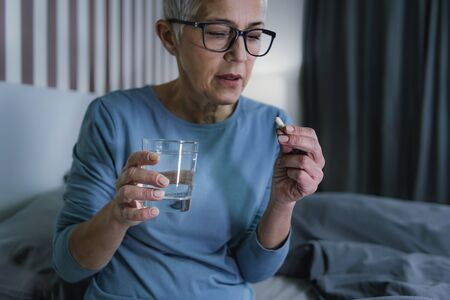 Sleepless Senior Woman Suffering from Insomnia, Holding Sleeping Pill and Glass of Water in Hands Reklamní fotografie