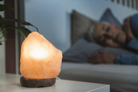 Mature woman sleeping with a Himalayan salt lamp in bedroom