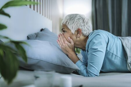 Circadian rhythm sleep disorder. Worried mature woman in bed staying awake late at night
