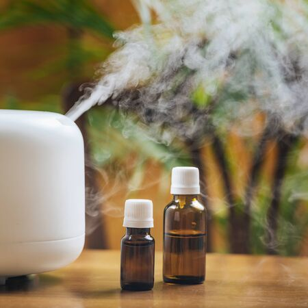 Natural essential oil bottles and aroma therapy diffuser on a wooden table. Scented steamy atmosphere in the background for comfortable living