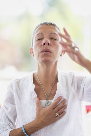 Mindful woman meditating, developing intuition. Hand gesture.