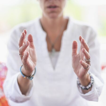 Mindful woman performing respect gesture with her hands. Spiritual awakening.