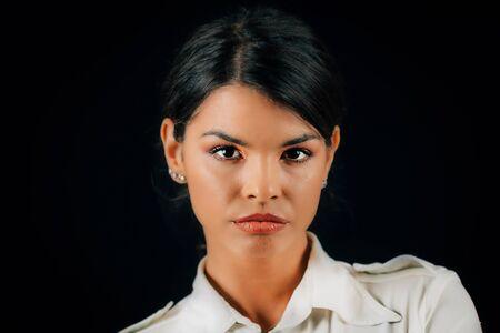 Emotion Jealousy. Portrait of a beautiful jealous young woman, studio portrait, black background