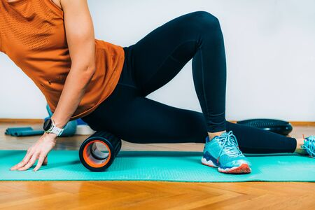 Woman Using Foam Roller Massager at Home. Banque d'images