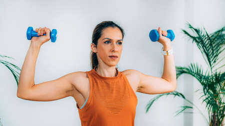 Exercising with Dumbbells at Home Фото со стока