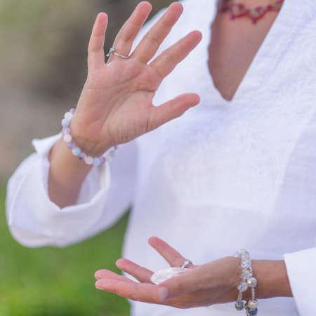 Female crystal healing therapist meditating, manifesting abundance with white selenite crystal. Energy work Archivio Fotografico
