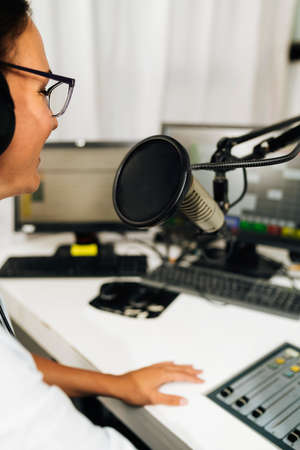 Attractive young millennial woman in front of microphone, using headphones, making an online radio podcast talk show.