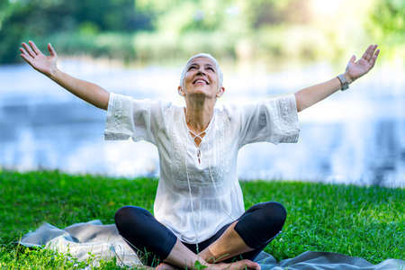 Mindful senior woman, feeling overwhelmed by beauty of the, meditating, sitting by the water with open arms