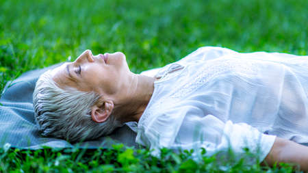 Mindful mature woman meditating by the water, lying down, feeling connected to the earth and nature Stock Photo