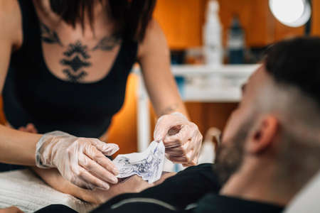 Tattooist removing stencil from a client`s arm