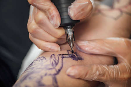 Hand of tattooist in rubber gloves drawing a tattoo with electric tattoo gun, close-up