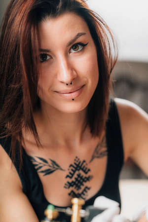 Professional female tattooist working in a tattoo studio Banque d'images