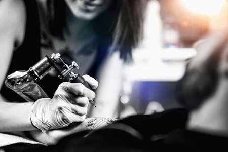 Professional female tattooist working in a tattoo studio 版權商用圖片