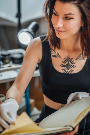 Female tattoo artist showing tattoo design to the client