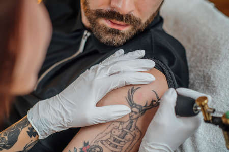 Tattooing safety during coronavirus crisis. Tattoo artist tattooing client with gloves and face mask in a tattoo studio during COVID-19 pandemic Banque d'images