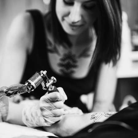 Female tattoo artist prepares tattoo machine for making a tattoo on a men's arm