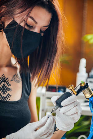 Female tattoo artist prepares tattoo machine for making a tattoo on a men's arm Banque d'images