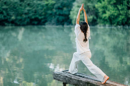 Yoga by the Lake – Young woman practicing Warrior 1 Pose or Virabhadrasana I 版權商用圖片