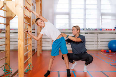 Physical activity class for children, using Swedish ladder for side stretching