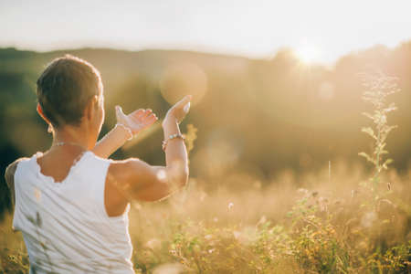 Meditating Outdoors, Connecting with Light - Making a gesture towards the sun, embracing sun rays, exchanging positive energy