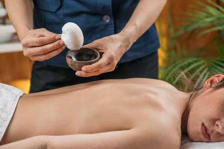 Kizhi or Herbal Bags Ayurveda Massage. Ayurvedic massage practitioner dipping cotton-wrapped herbal bundle into aromatic oil.