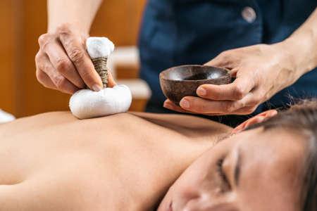 Kizhi Ayurveda Massage with Herbal Pads. Woman lying with eyes closed enjoying Ayurvedic massage treatment in wellness spa center. Stock fotó