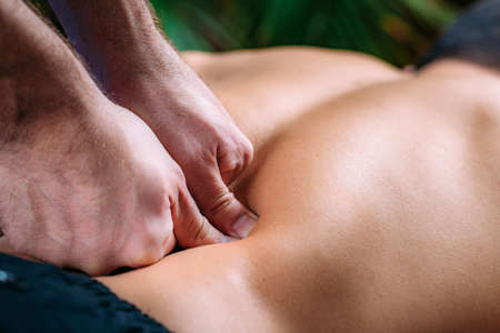 Discus Hernia manual massage treatment. Physical therapist massaging lower back. Stock Photo
