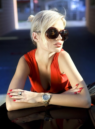 fashionable beautiful blonde in sunglasses and red dress