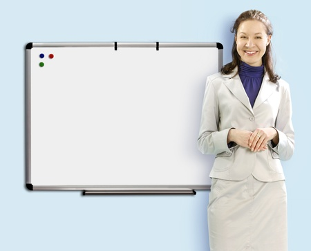 smiling teacher near school board in white suit