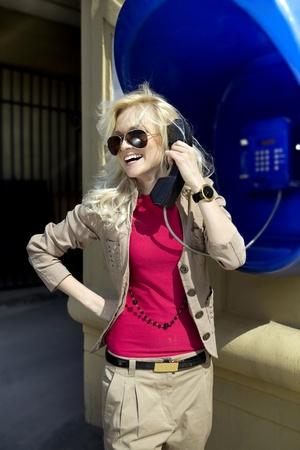 blonde speaks by payphone on street of Kiev