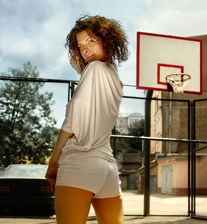 curly girl on basketball platform in white clothes photo