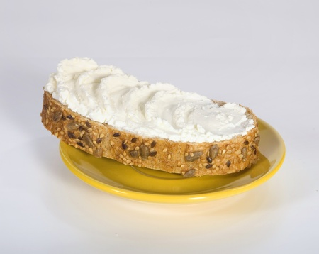 Appetizing sandwich with butter on the yellow saucer