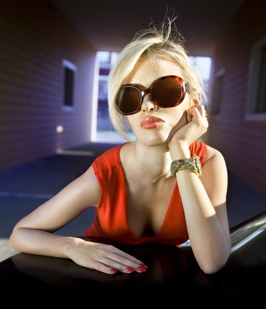 face of fashionable blonde in sunglasses and red dress Stock Photo