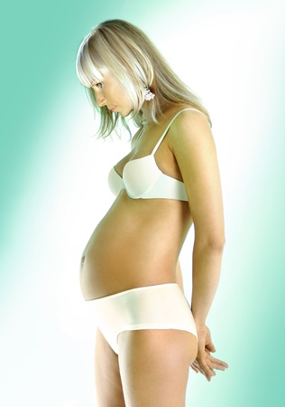 beautiful pregnant woman in white underwear on light background photo