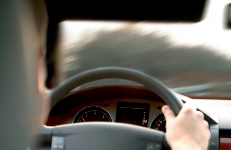 driver holds wheel in car and goes on road Standard-Bild