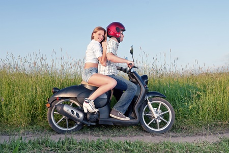 couples outdoors: Young couple on motor scooter