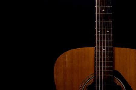 Close up detail of orange acoustic guitar
