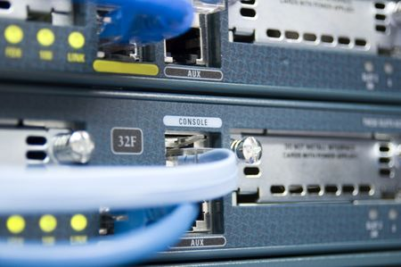 The face of a communications router with data and console cables attached. Imagens