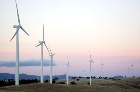 Wind generators sit separated along the hilltops of a modern wind farm. Stock Photo