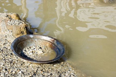 searching for: A prospectors Gold Pan left by the river.