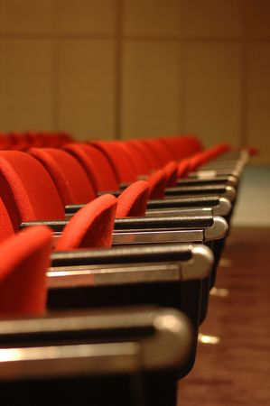 A line of red theatre chairs - short depth of field. Stock Photo