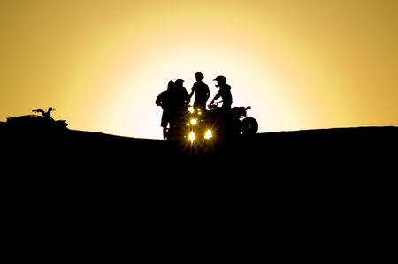 The silhouette of two friends with their four wheel motorbike
