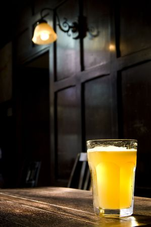A lone beer glass in a darkened atmospheric English Pub Stock Photo