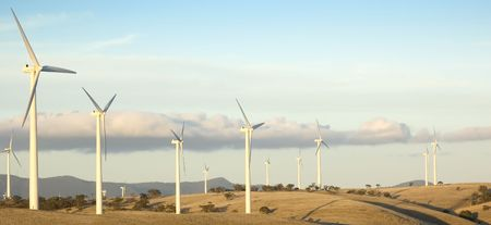 Large wind turbines line up along the hilltop as part of an energy producing windfarm. Stock Photo