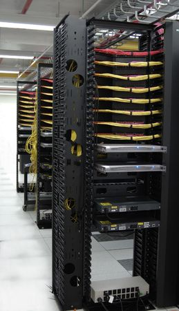 A data center where each row of servers has a KVM server control system mounted at the end of each row. Stock Photo