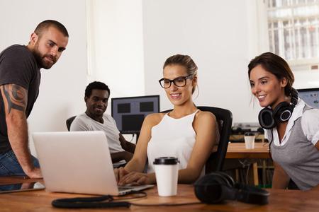 jovenes empresarios: Equipo de j�venes empresarios mirando un ordenador port�til en una oficina de empresa que comienza, Foto de archivo
