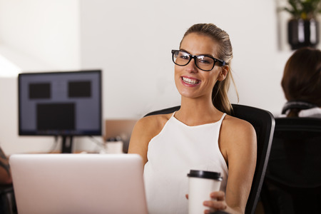 startup: Young woman entrepreneur sitting at her computer and smiling in her startup office Stock Photo