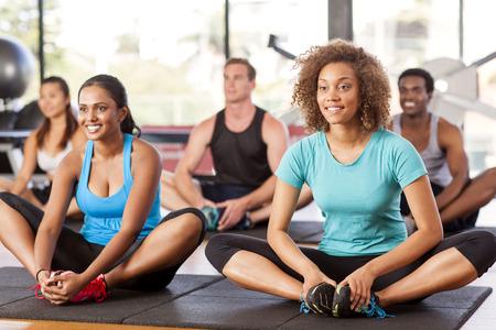 Groupe multi-ethnique qui se étend dans une salle de sport avant leur classe d'exercice