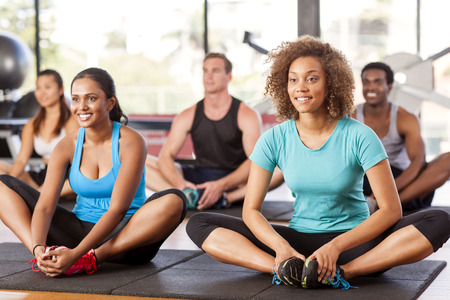 multi ethnic groups: Multi-ethnic group stretching in a gym before their exercise class Stock Photo