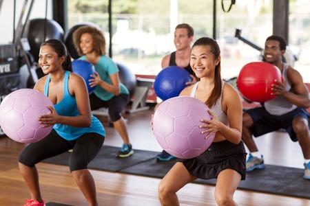 Multiethnische Gym Class tun Kniebeugen mit Medizinbälle